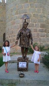 Una estatua viviente con dos niñas.